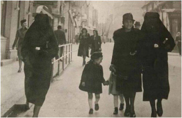 A Muslim woman covers the yellow star of her Jewish neighbour with her veil to protect her from prosecution. Sarajevo, former Yugoslavia 1941