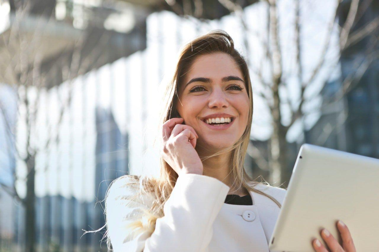businesswoman-holding-tab-and-smiling